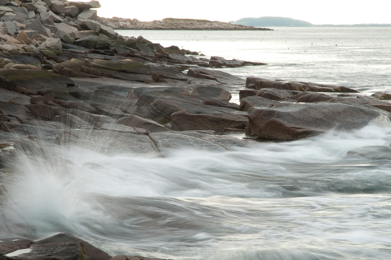 A peaceful sea wets the rocks of Halibut Point, Rockport, MA